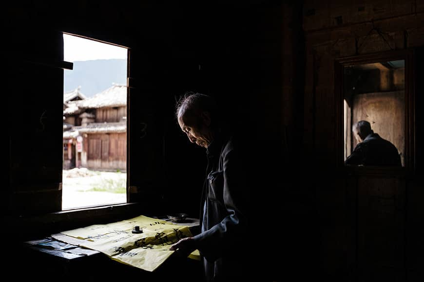 A Chinese Calligrapher producing signs using traditional calligraphy in his shop, The Calligrapher's Shop, Main Square, Shaxi, China