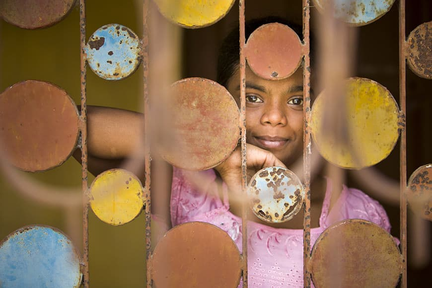 A girl posing behind decorative bars at beside the front door of her family home, Jote, Shibrampur, Kolkata, India