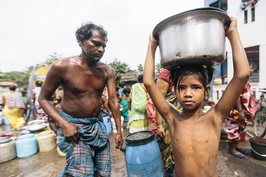 A girl carrying a bucket of water on her head after filling it from a water truck, Tangra slum, Dhipi, Kolkata, India, Tangra slum, Dhipi, Kolkata, India