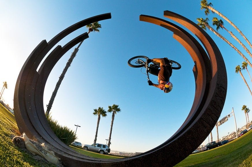 Rider: Danny MacAskill, Trick: Back flip , Description: Danny MacAskill doing a back flip off a sculpture in downtown San Diego, California.