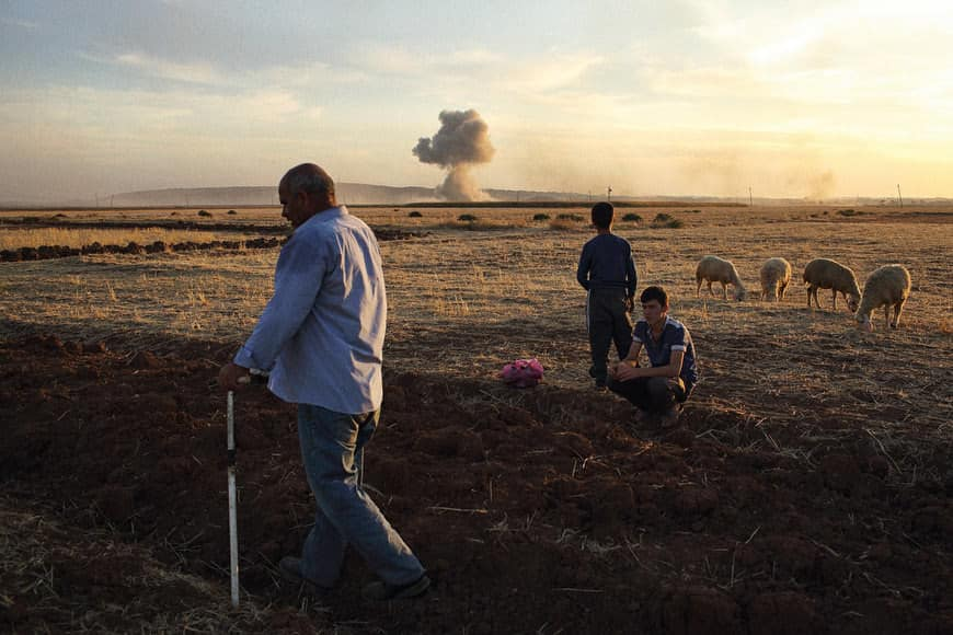 A sheep herder and his two sons in a field outside Mursitpinar on the Turkish border with Syria moments after a massive missile exploded in the east of Kobani where intense fighting between militants from the Islamic State (IS) and Kurdish YPG units raged today as intermittent air strikes (much smaller than this one) by the U.S.-led coalition fell on IS positions. The crowds that gathered were calm today in comparison to previous days which have seen clashes between Kurds and Turkish security forces. Morale of the crowds was lifted late in the day with two air strikes that dwarfed those of the days prior. CREDIT: Andrew Quilty for The Wall Street Journal