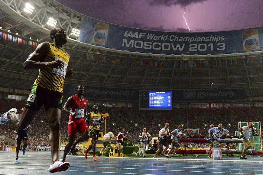 Jamaica's Usain Bolt (L) wins the100 metres final at the 2013 IAAF World Championships at the Luzhniki stadium in Moscow on August 11, 2013 while a lightning strikes in the sky. Bolt timed a season's best 9.77 seconds, with American Justin Gatlin claiming silver in 9.85sec and Nesta Carter, also of Jamaica, taking bronze in 9.95sec.  AFP PHOTO / OLIVIER MORIN