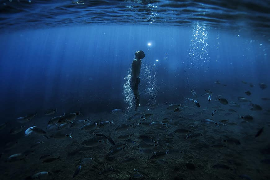a man swims in apnea around fishes in a creek of Portofino , on 8 September, 2015. AFP PHOTO / OLIVIER MORIN
