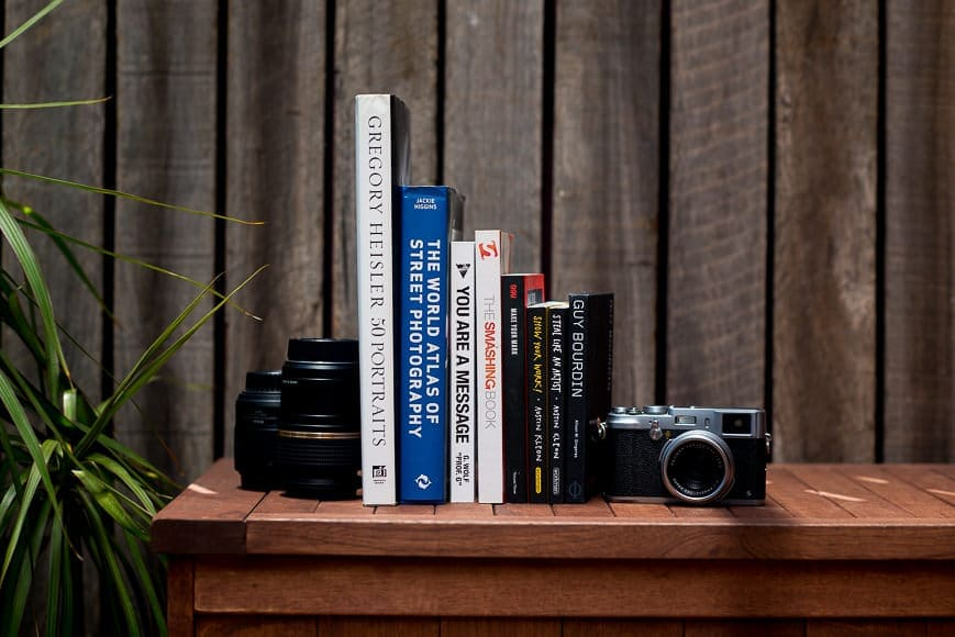Photos of the Best photography books sitting next to a camera and a lens