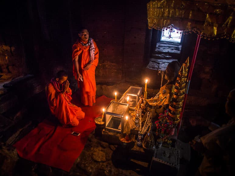 14 MARCH 2105 - SIEM REAP, SIEM REAP, CAMBODIA: Buddhist monks pray in a prayer room in Bayon, one of the temples in Angkor Thom, a part of the Angkor Wat complex. Bayon was built in 12th or 13th century CE.  PHOTO BY JACK KURTZ