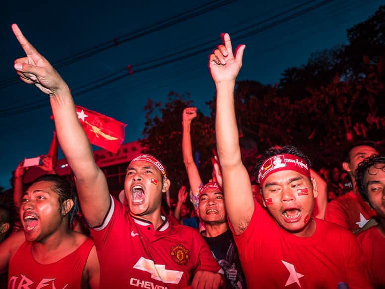 09 NOVEMBER 2015 - YANGON, MYANMAR: Men react to elections' officials announcing vote results during the victory celebration at NLD headquaters Monday. Thousands of National League for Democracy (NLD) supporters gathered at NLD headquarters on Shwegondaing Road in central Yangon to celebrate their apparent landslide victory in Myanmar's national elections.     PHOTO BY JACK KURTZ