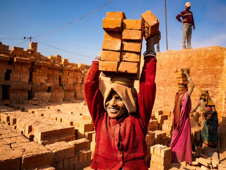 03 MARCH 2017 - BAGMATI, NEPAL: A woman balances finished bricks on her head to carry them to a truck at a brick factory in Bagmati, near Bhaktapur. There are almost 50 brick factories in the valley near Bagmati. The brick makers are very busy making bricks for the reconstruction of Kathmandu, Bhaktapur and other cities in the Kathmandu valley that were badly damaged by the 2015 Nepal Earthquake.   PHOTO BY JACK KURTZ