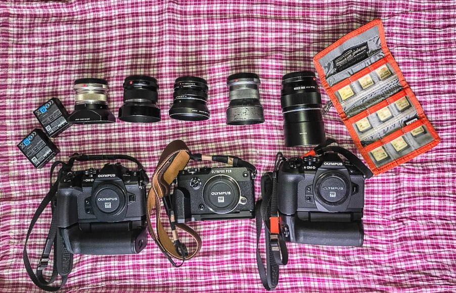 My gear, bottom, E-M1 Mark II, Pen-F, E-M1 Mark II. Top, BLH-1 batteries for E-M1 Mark II, 12mm f2, 25mm f1.8, 17mm f1.8, 45mm f1.8, 75mm f1.8, SanDisk SD cards in a Think Tank card wallet. All on top of a red and white Krama (Khmer scarf). PHOTO BY JACK KURTZ