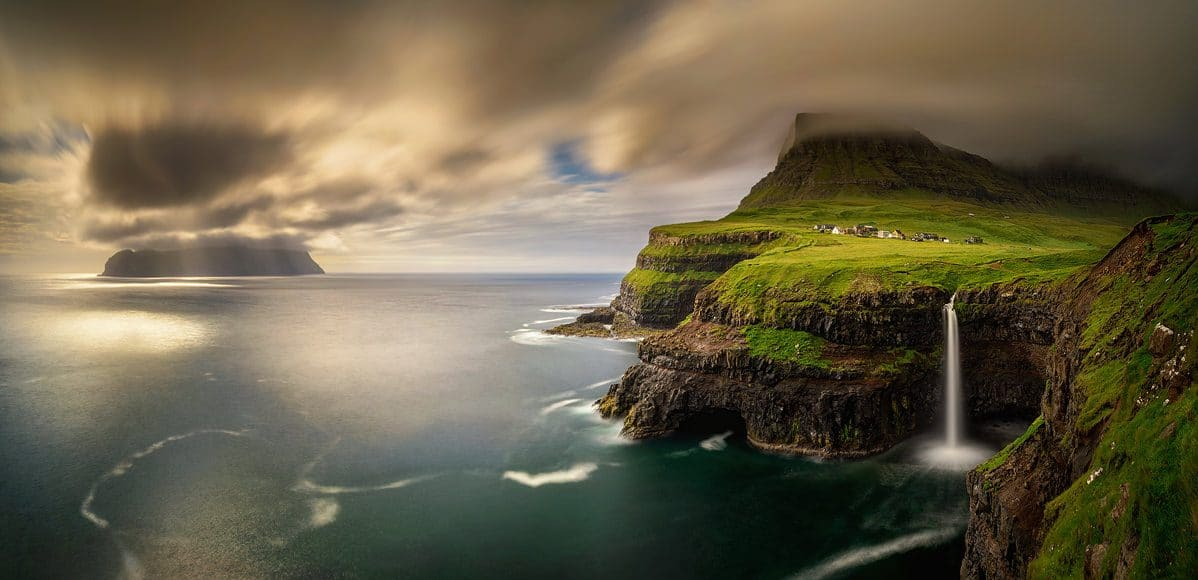 Panorama of Gasadalur village and cloudy Mykines island in sunset, Faroe Islands