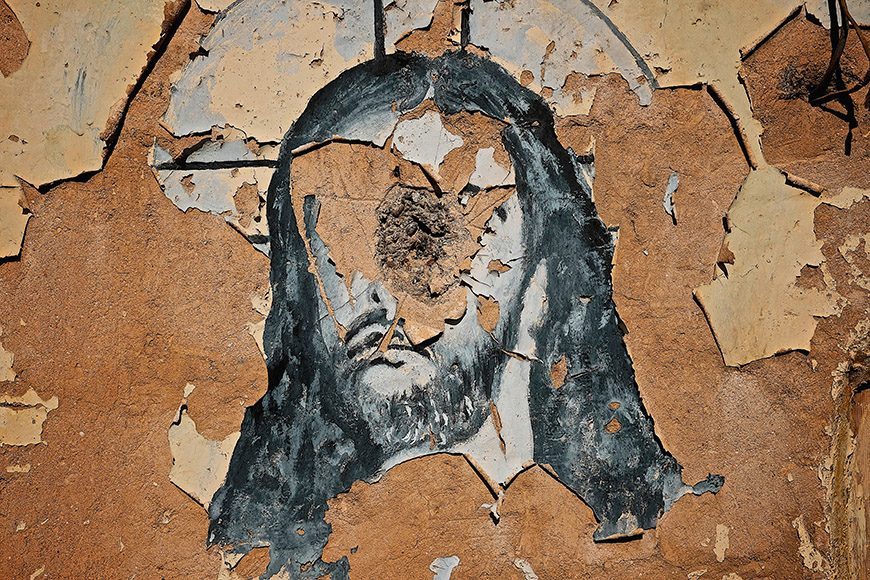 A mural of Jesus destroyed by Islamic State militants during their occupation of the Christian city of Bartallah, Iraq located immediately outside of the city of Mosul on February 3, 2017. The church was burnt and used as a defensive position for the militants against the Iraqi military. The town is deserted and used as a base for Iraqi and Coalition military until the offensive on the city of Mosul is completed and established safe for residents to return. (Photo by Osie Greenway)