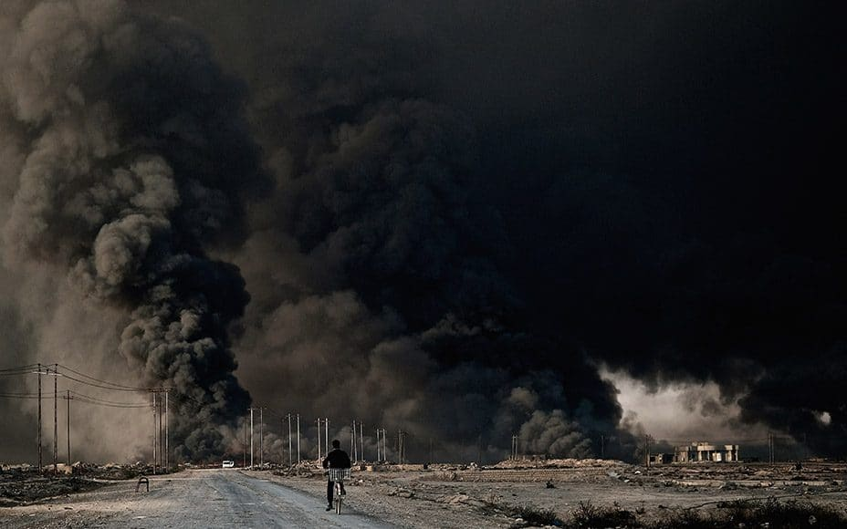 Ahmed 19, rides his bicycle down a deserted road towards the mammoth burning oil wells set ablaze by ISIS militants to obscure their retreat from the area from Iraqi and Coalition warplanes in Qayyarah, Iraq on November 13, 2016.(Photo by Osie Greenway)