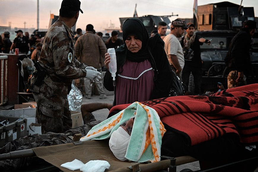 An Iraqi woman who fled her neighborhood in East Mosul, Iraq with her wounded husband after being caught in heavy clashes between Iraqi security forces and Islamic state militants watches silently as her husband dies at a casualty collection point set up by the Iraqi military medical staff and foreign volunteer medics. The man's skull was cracked leaking brain fluid uncontrollably on November 5, 2016. (Photo by Osie Greenway)