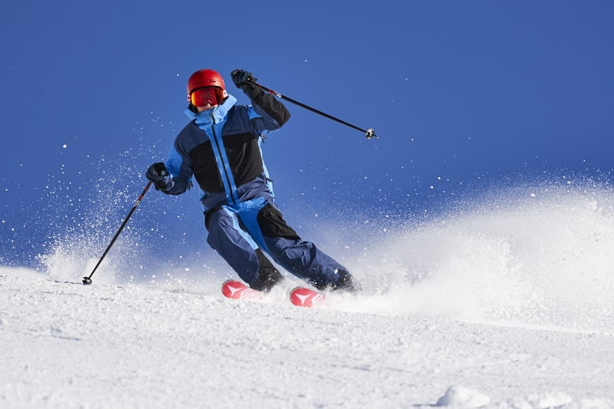 the right shutter speed captures motion with good image exposure. Long focal length lens used at fast shutter speed to freeze skiier.