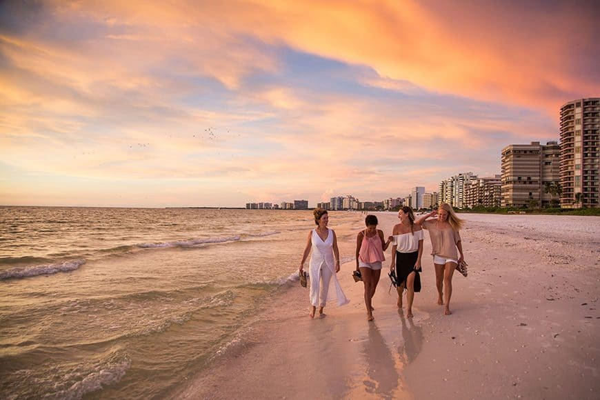 Four beautiful women walk the beaches on Marco Island, south of Naples Florida, during a perfect west coast of Florida sunset for an advertising campaign photoshoot for an agency specializing in luxury real estate.