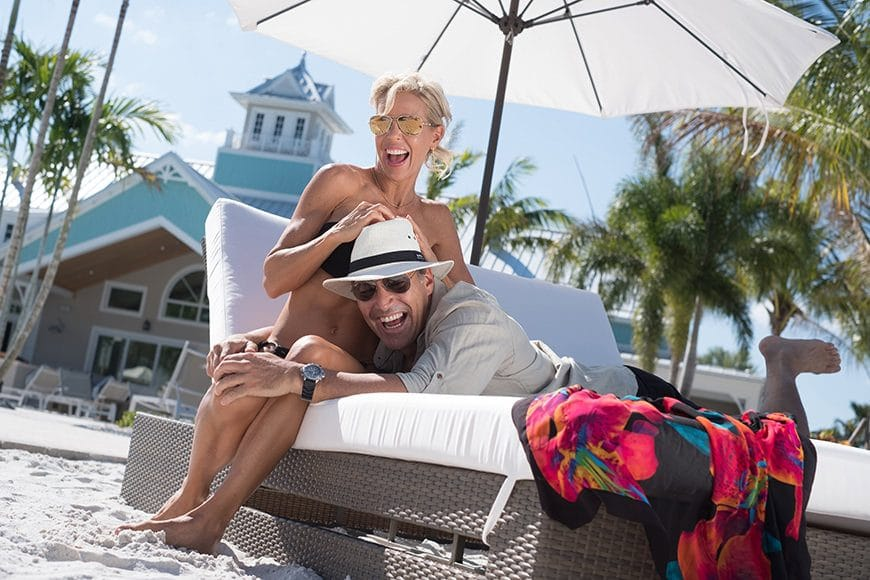 Professional models have a moment while joking around on a recliner at the sandy beach front of the resorts swimming pool. The photo was made as part of a luxury lifestyle advertising campaign for a resort community in Naples Florida.