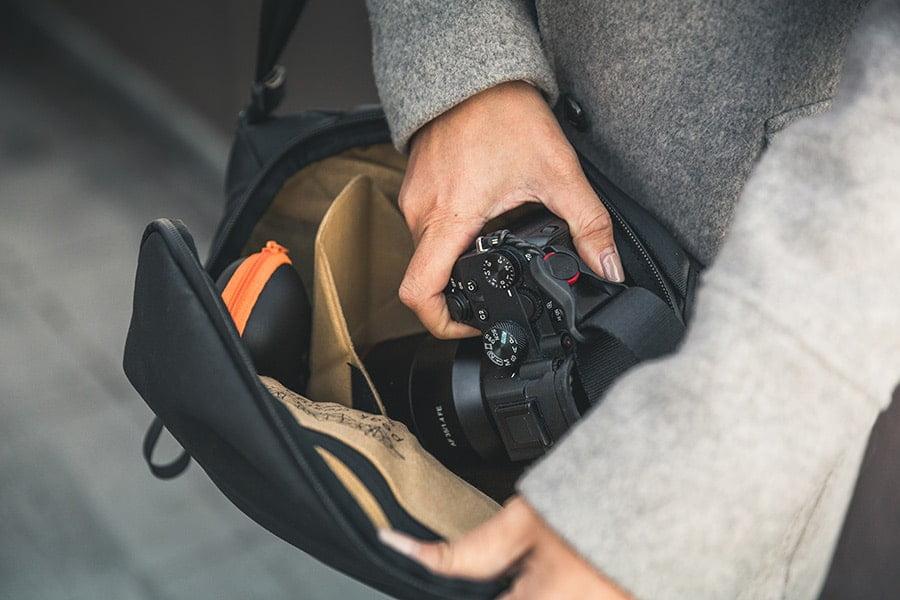 Man removing SLR from Peak Design Everyday Sling 5L