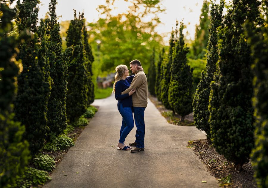 Couple embracing on path lined with trees using Sony A7R3 and Sony 135mm lens