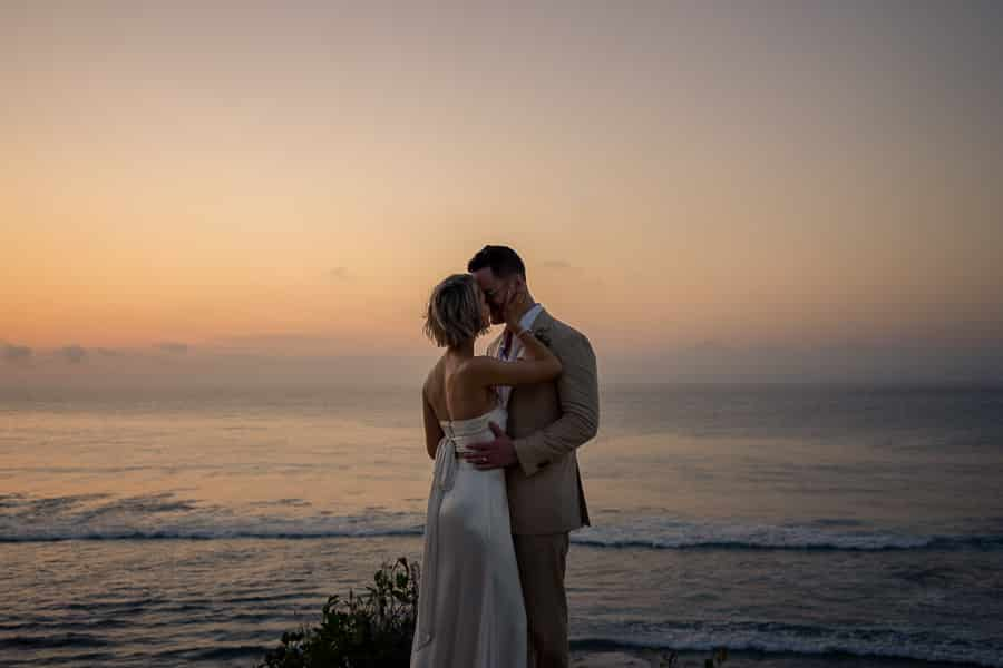 newly wed couple embracing on cliff edge at sunset