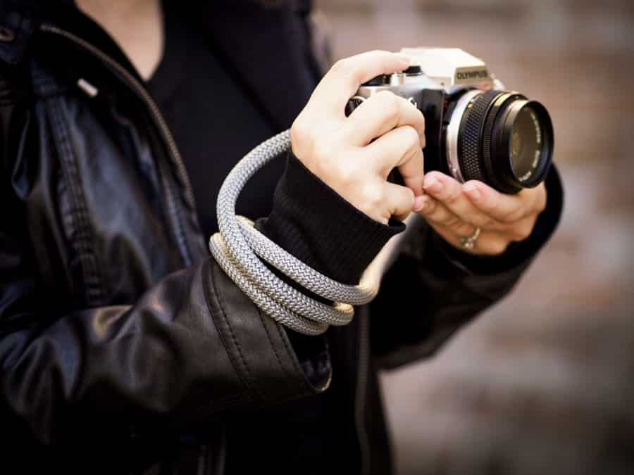 A photographer wraps her rope strap around her hand to secure her camera.