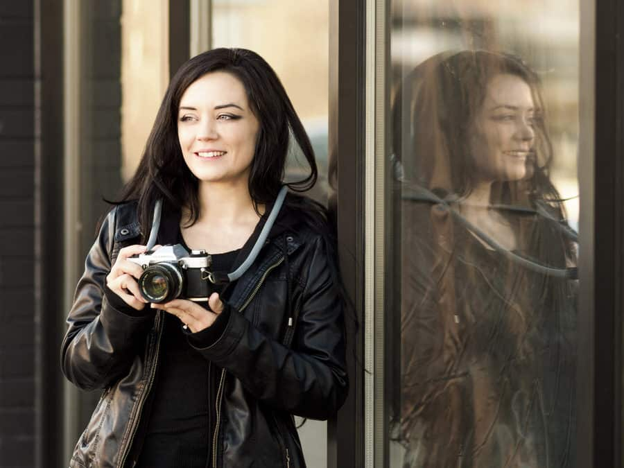 A photographer leans against a reflective shop window holding her film camera secured by a rope style camera strap.