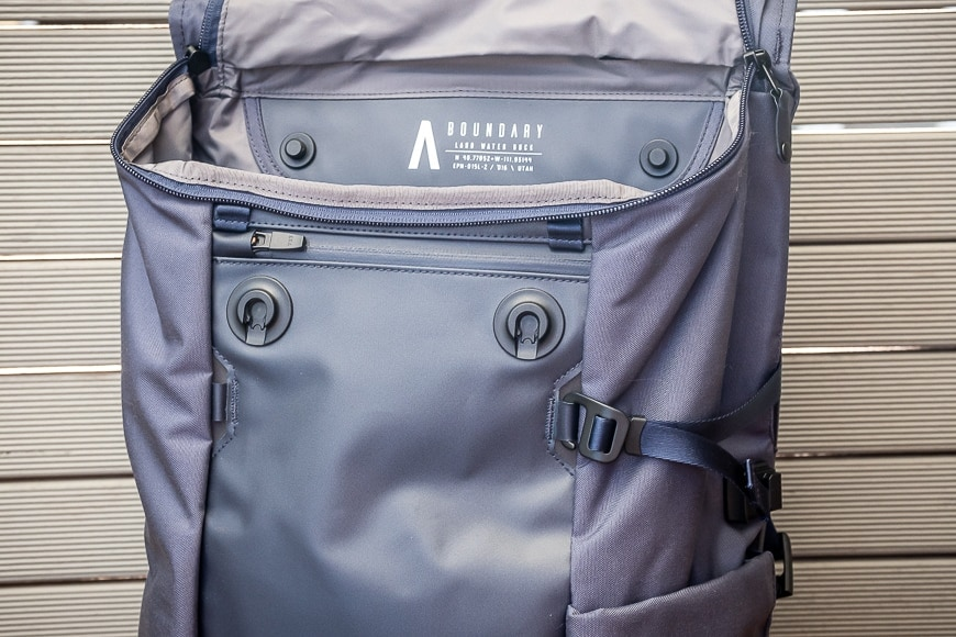 A magnetic latch system secures both the camera insert inside the bag and the main flap on the outside.