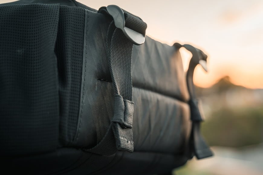 The cargo straps at the base of the Instinct X-Pac Pro Camera Sling Bag assist with external carry and to decrease the bags width when you don't need the full size.