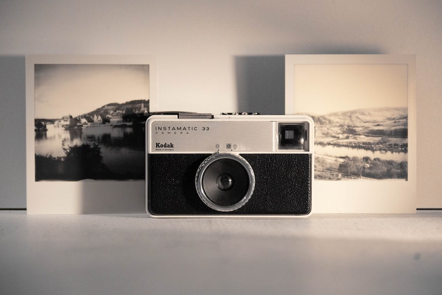 Kodak camera sitting sharp with polaroids in the background