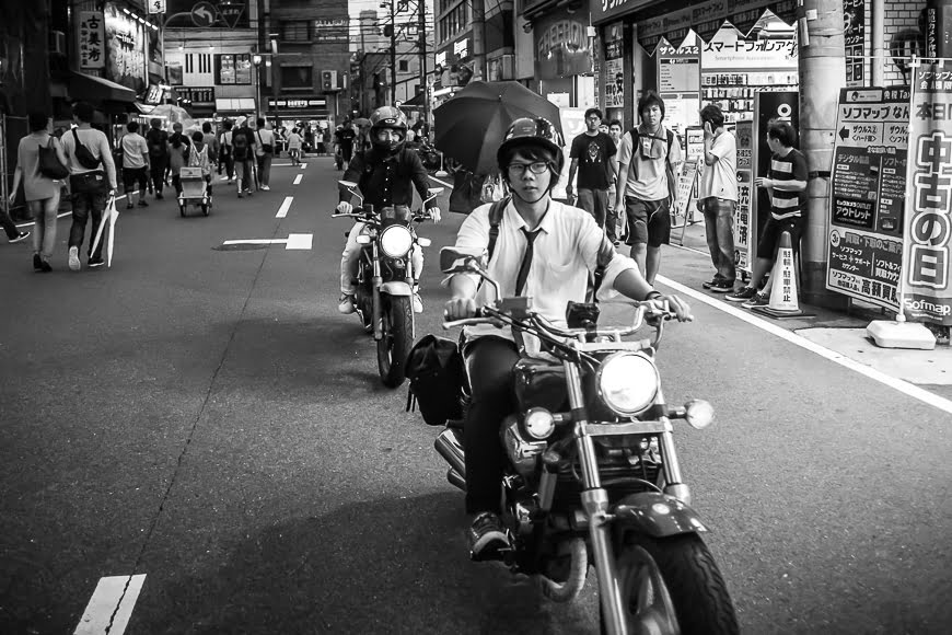 Black and white photo of a busy Japanese street with a man on a motor bike