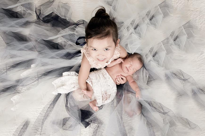 Family members can be used in photos as newborn photography props.