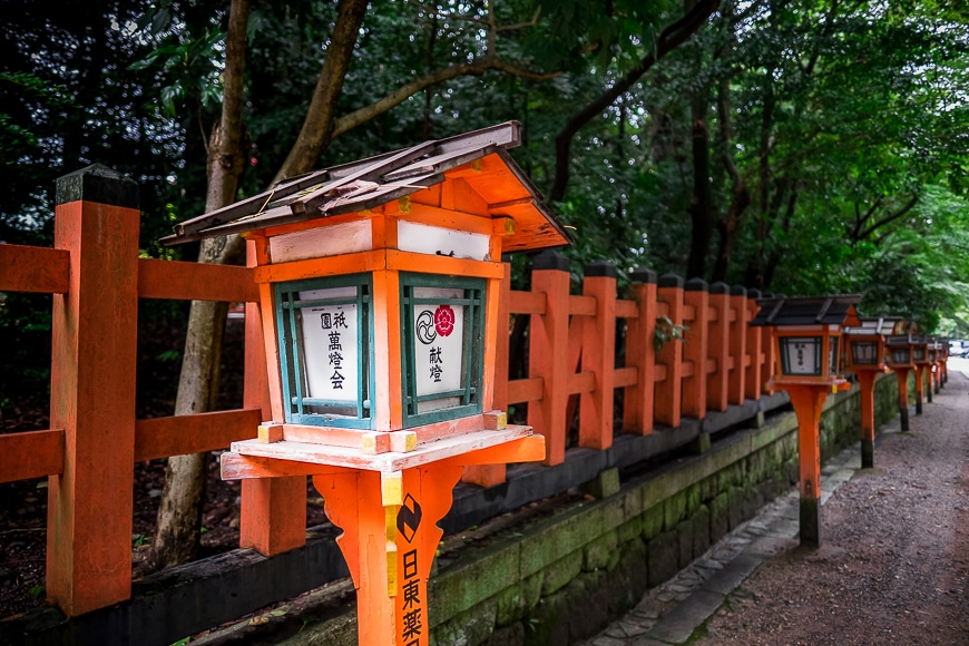 An orange fence lined with Japanese letter boxes