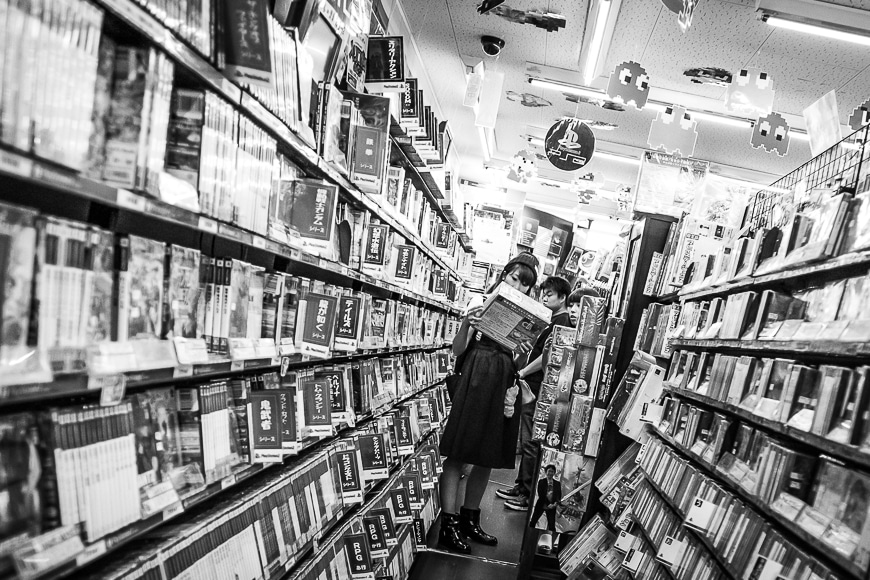 Two women in a Japanese library aisle