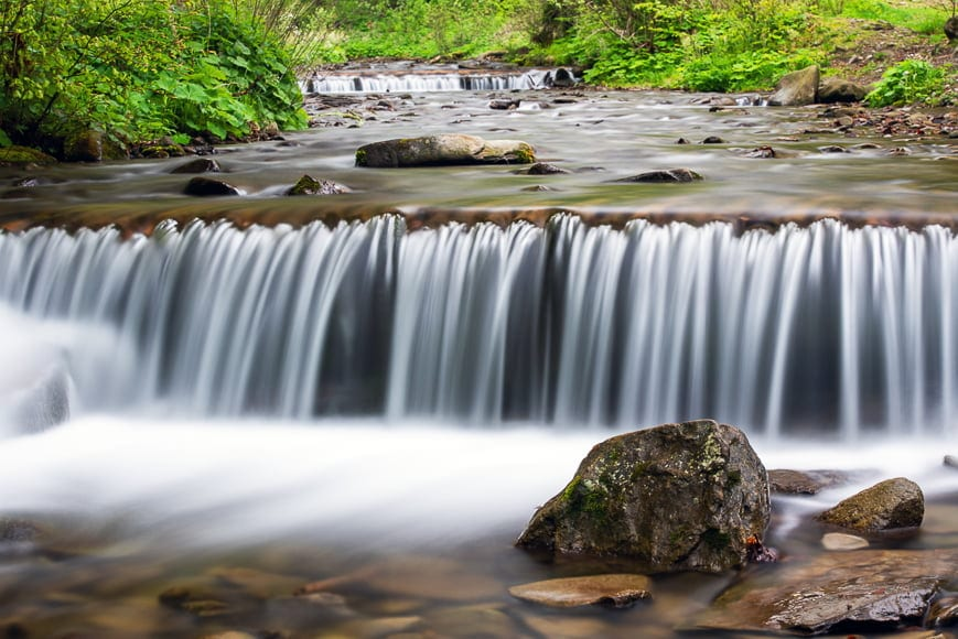 Capture waterfalls in forest photography using slow exposure times.