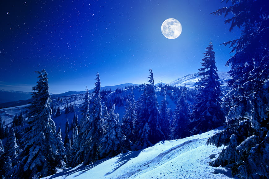 Moon and stars over snowy mountains.