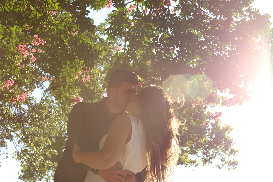 photo - spring shot of couple kissing under flowers