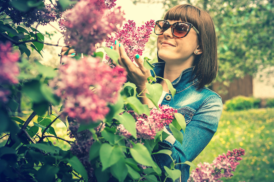 A beautiful photo of a lady smelling flowers