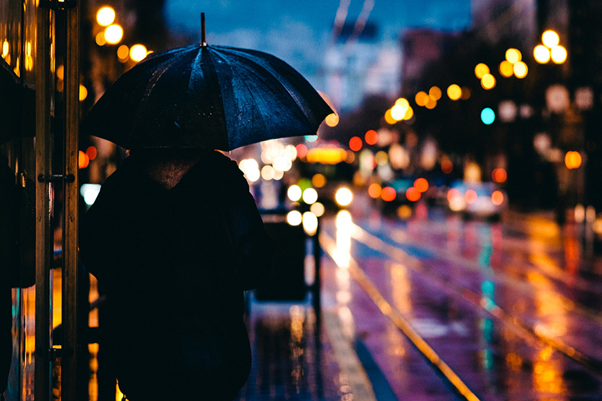 Photography for beginners - person with umbrella standing on a busy street at night