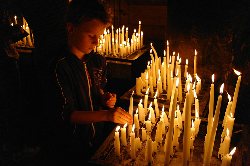 Photography basics - boy standing with many lit candles