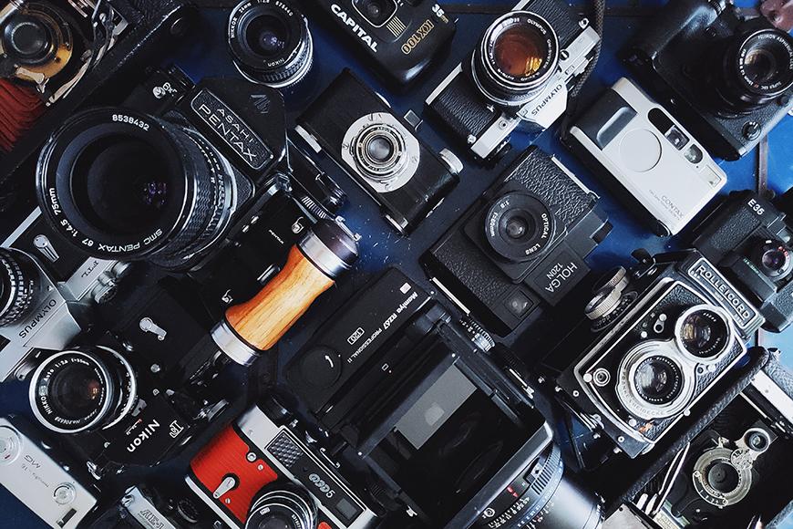 Photography basics - flat lay of an assortment of cameras