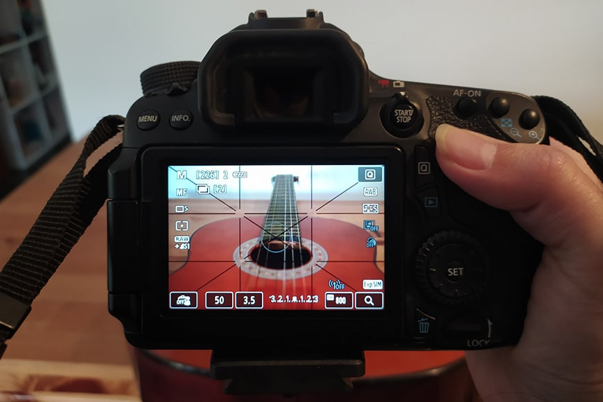 The LCD screen of a Canon camera showing a guitar image