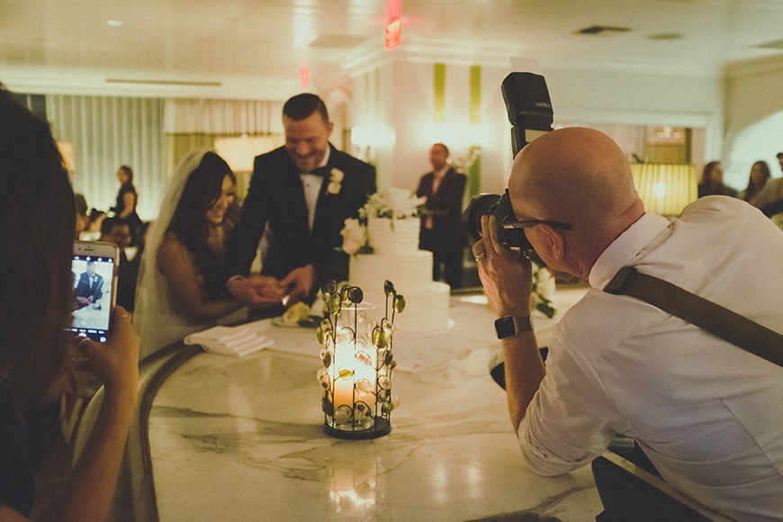 A photographer taking a photo of a married couple with a DSLR camera