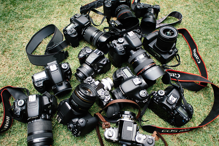 How to get into photography - many cameras in a pile on the grass