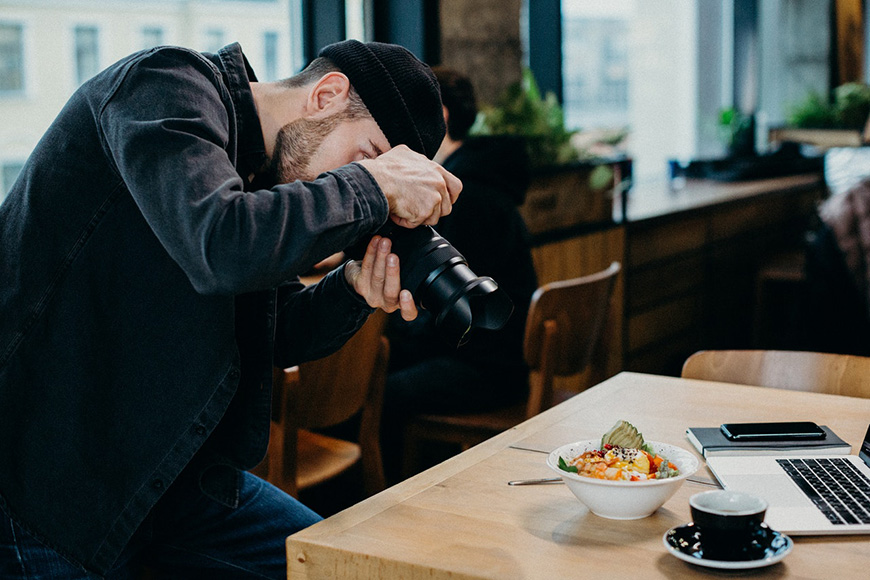 A man with a camera taking a photo of food