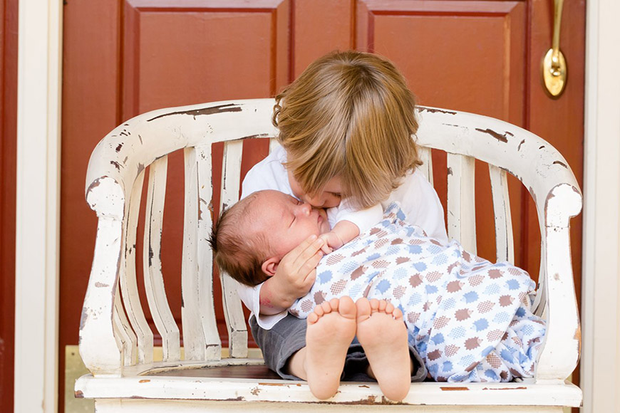Toddler holding and kissing an infant