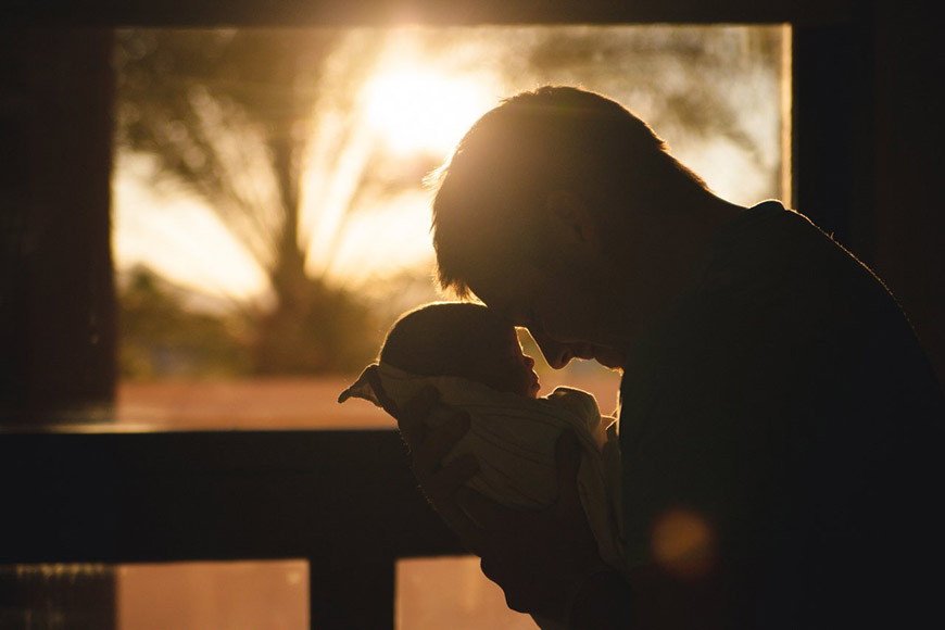 Father holding an infant against sunset