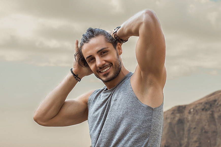 A male model posing with his hands in his hair