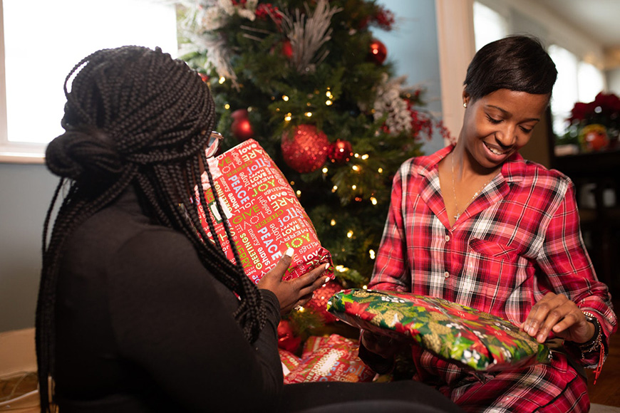 Two women opening presents by a Christmas tree