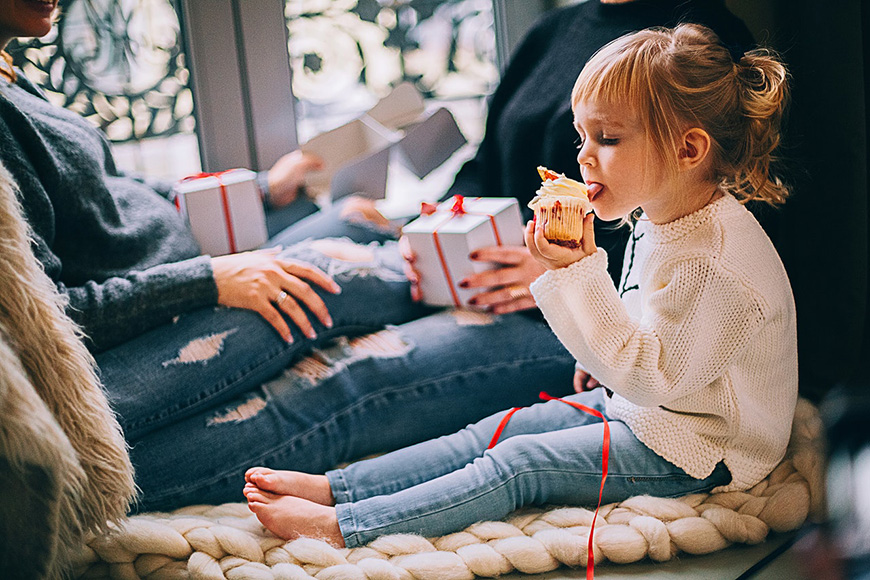 Little girl sitting eating a cupcake