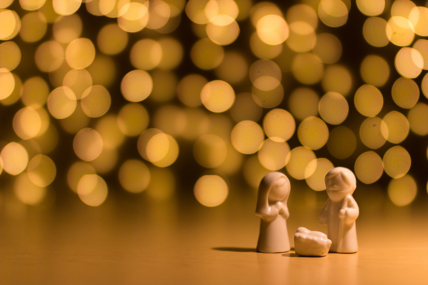 Small nativity statues in front of Bokeh effect lights