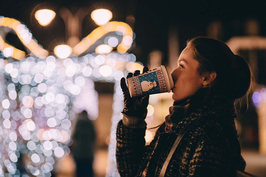 Women having a hot drink at night in front of lights