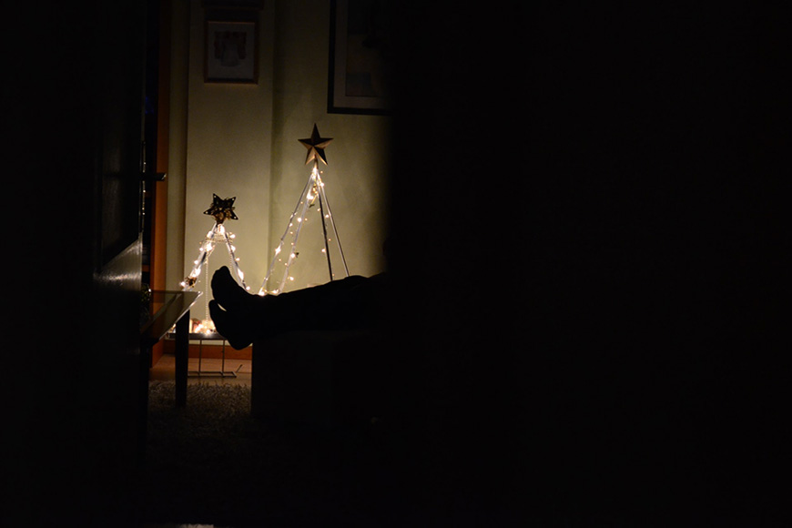 A person laying in the dark with only lights from decorations on